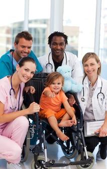 Menina bebê, em, um, cadeira rodas, com, equipe médica