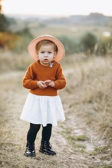 Menina bebê fofo fora no parque, tempo de outono