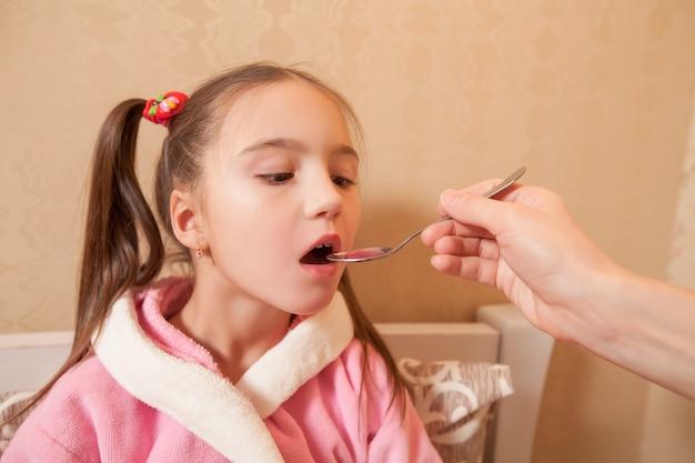 Menina bebe mistura com uma colher
