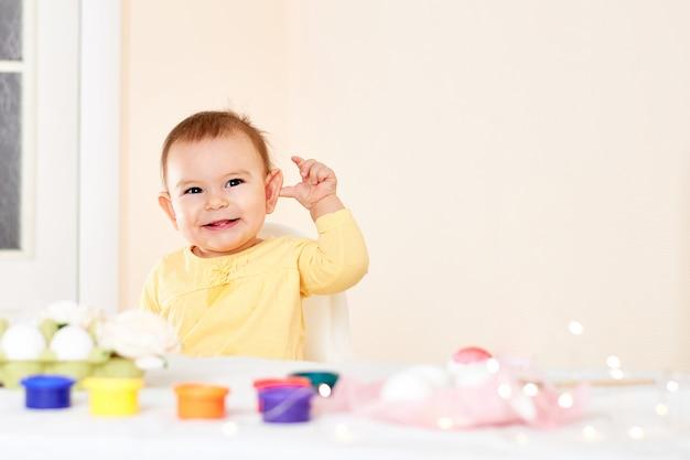 Menina bebê, sentando, tabela, e, quadro, pintando feriado, ovos páscoa, sorrindo, feliz, infancia