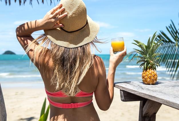 Menina bebe suco na praia