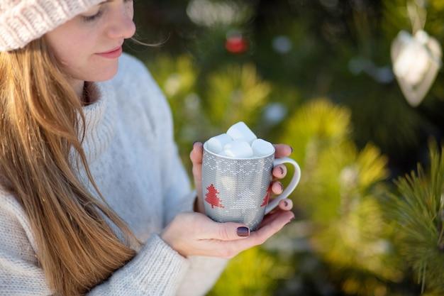 Menina bebe uma bebida quente com marshmallows no inverno na floresta.
