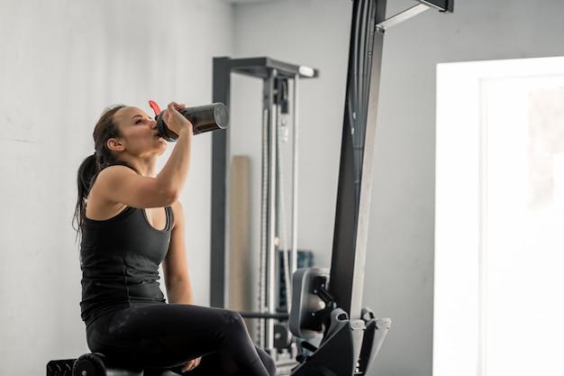 Menina bebendo água no ginásio depois de treino