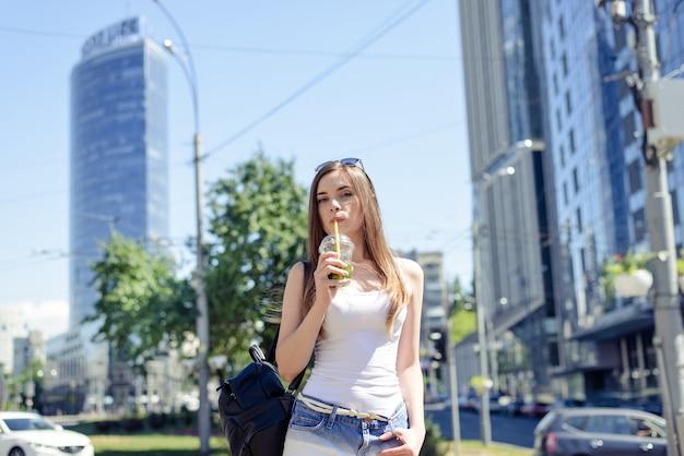 Menina bebendo bebida segurando um copo de plástico na mão