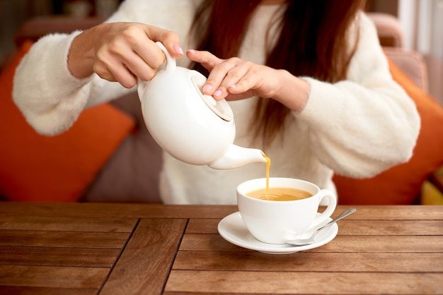 Menina bebendo chá de desintoxicação de ervas no café xícara branca de chá de espinheiro-mar na mesa no café