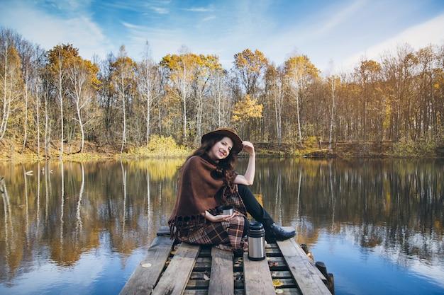 Menina, bebendo chá em uma ponte de madeira em um lago