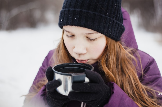 Menina, bebendo chá ou bebida de uma garrafa térmica, caminhada no inverno, caminhadas, inverno, roupas de inverno