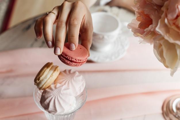 Menina bebendo chá ou café da manhã. mãos fecham e bolo