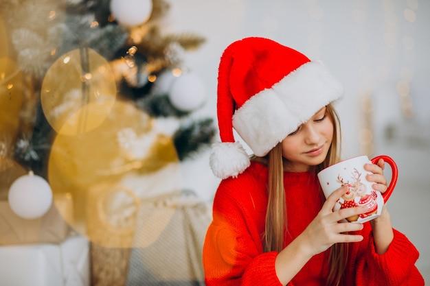 Menina bebendo chocolate perto da árvore de natal