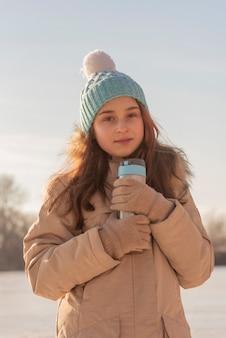 Menina bebendo da xícara térmica no inverno. menina bebendo chá em uma garrafa térmica no inverno
