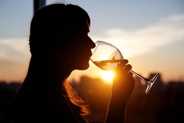 Menina bebendo de um copo ao pôr do sol.