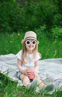 Menina bebendo delicioso smoothie de morango com leite e sorvete, ao ar livre, conceito de verão, comida saudável