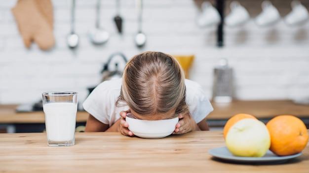 Menina bebendo leite da tigela