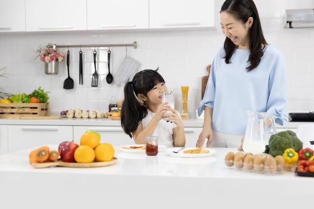 Menina bebendo leite na cozinha em casa