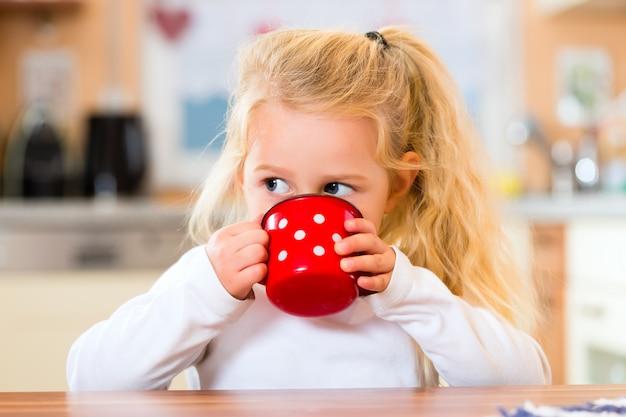 Menina bebendo leite na cozinha