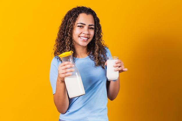 Menina bebendo um copo de leite e segurando a garrafa cheia.