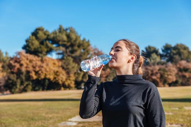 Menina beber água após o treino