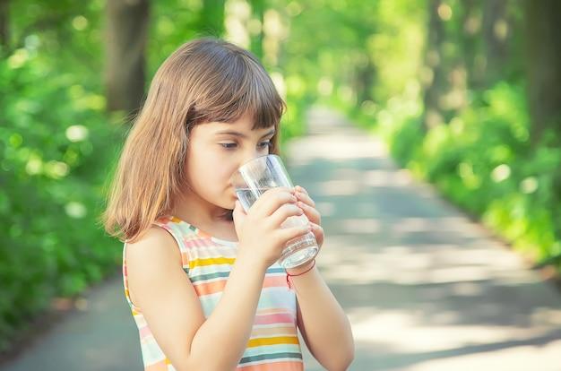 Menina beber água de um copo