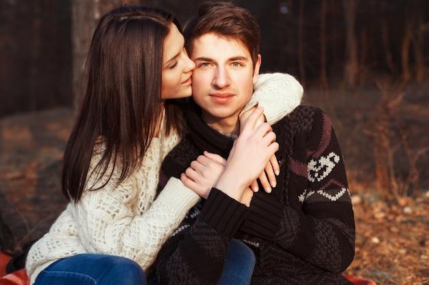 Menina beijando a bochecha de seu namorado