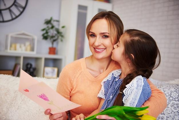 Menina beijando a mamãe na bochecha