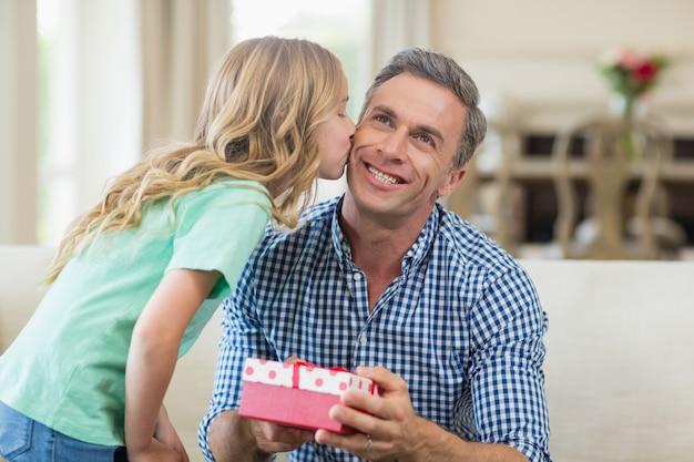 Menina beijando o pai na bochecha na sala de estar