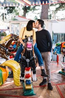 Menina, beijando, seu, namorado, em, a, merry-go-round