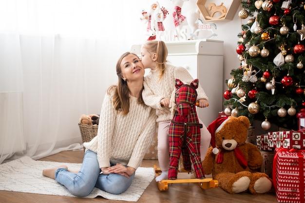 Menina beijando sua mãe em casa perto de caixas de árvore e presente de natal