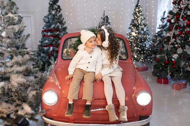 Menina beijando um menino enquanto está sentada no carro vermelho perto da árvore e luz de natal