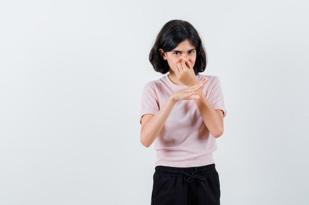 Menina beliscando o nariz devido ao mau cheiro em camiseta rosa e calça preta e parecendo preocupada