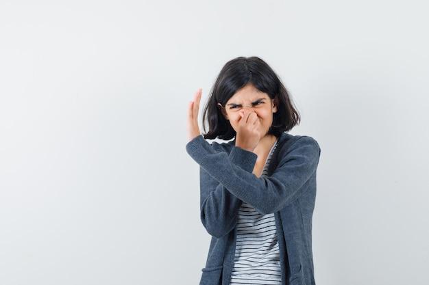 Menina beliscando o nariz devido ao mau cheiro na camiseta, jaqueta e parecendo enojada.