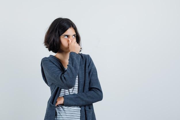 Menina beliscando o nariz devido ao mau cheiro na camiseta, jaqueta