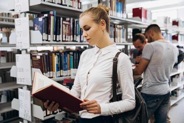 Menina bem pensativa parece estudante de pé com livro na biblioteca de uma universidade