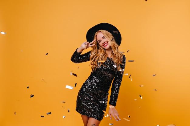 Menina bem torneada e fascinante no chapéu, se divertindo na festa. senhora loira elegante dançando sob confete.