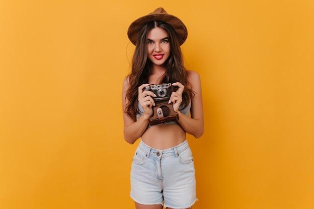 Menina bem torneada usa short branco segurando a câmera enquanto está de pé no espaço amarelo