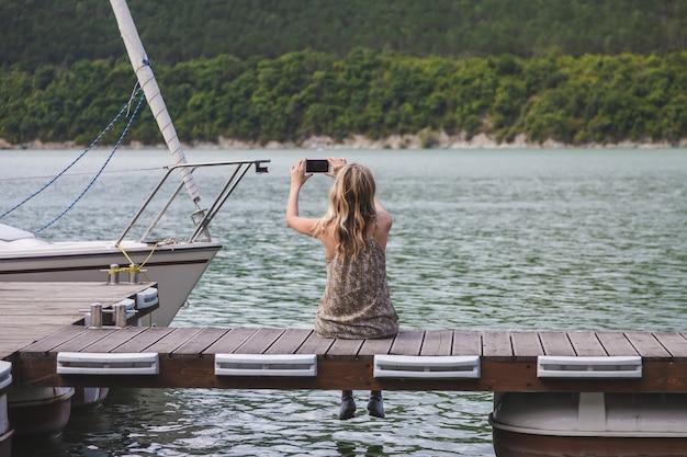 Menina blogger viajante senta-se em um píer e tira fotos em um smartphone
