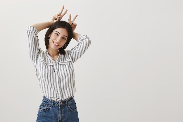 Menina boba alegre mostrando gesto de orelha de coelho atrás da cabeça e sorrindo