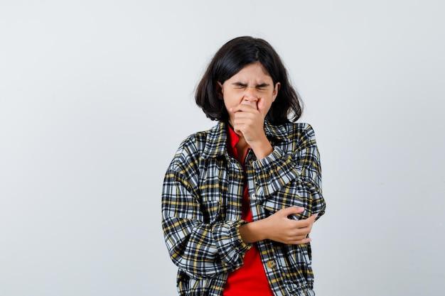 Menina bocejando com a mão na boca na camisa, jaqueta e parecendo com sono, vista frontal.