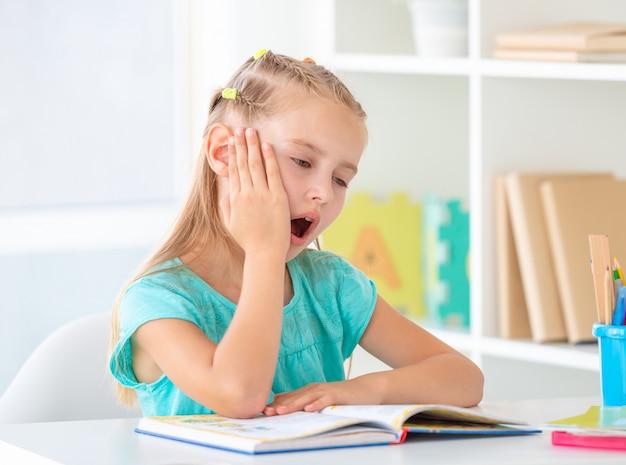 Menina bocejando na frente do livro aberto