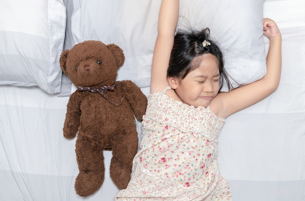 Menina bocejar e dormir na cama com boneca de urso de pelúcia