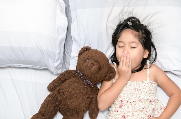 Menina bocejar e dormir na cama