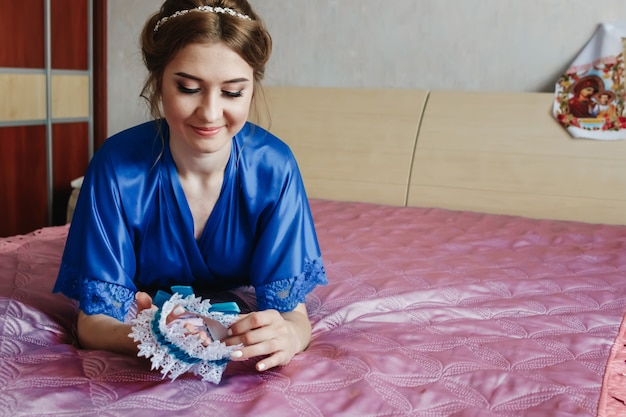 Menina bonita, a noiva em um roupão no fundo do apartamento. casamento, reunião de noiva, criação de família.