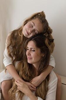 Menina bonita, abraçando a mãe na sala de estar em camisa branca.