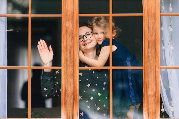 Menina bonita, abraçando a mãe sorridente e olhando para a janela.