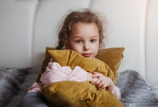 Menina bonita abraçando um travesseiro amarelo na cama