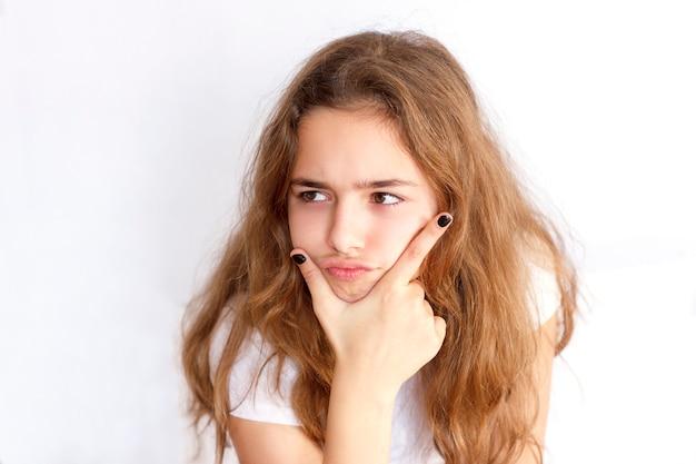 Menina bonita adolescente com cabelo comprido faz cara engraçada muito zangada