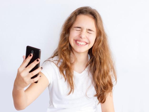 Menina bonita adolescente com cabelo comprido faz selfie com cara engraçada rindo