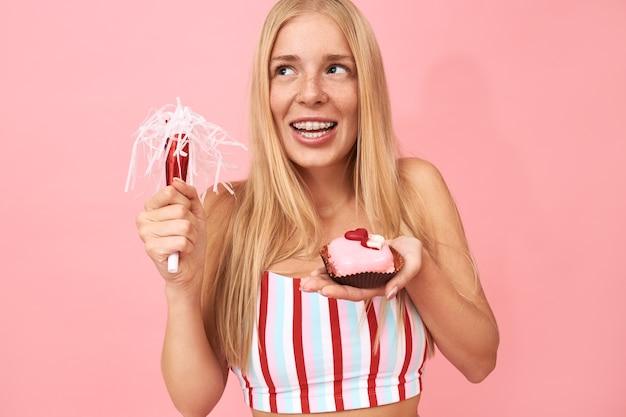 Menina bonita adolescente com cabelo liso e aparelho nos dentes comemorando aniversário, posando isolada com soprador de festa e doce sobremesa, fazendo um desejo, tendo uma expressão facial de alegria sonhadora