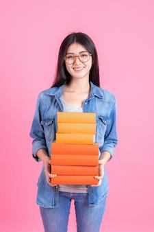 Menina bonita adolescente de retrato segurando a pilha de livros e smiley em rosa, conceito de teenge de educação