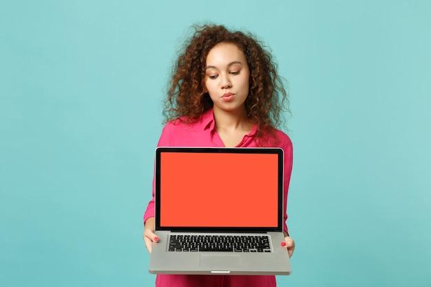 Menina bonita africana com roupas casuais segurar o computador laptop pc com tela vazia em branco isolada sobre fundo azul turquesa no estúdio. emoções sinceras de pessoas, conceito de estilo de vida. simule o espaço da cópia.