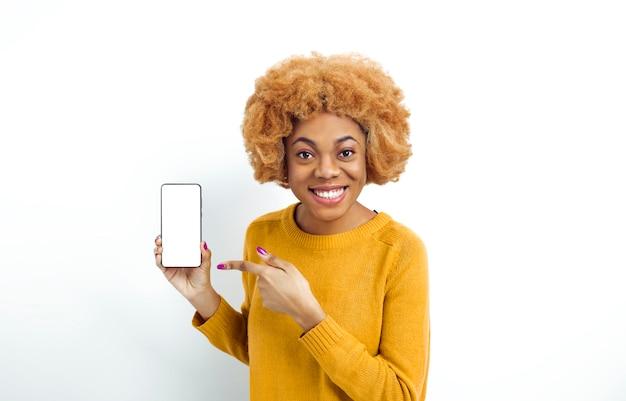 Menina bonita africana detém um smartphone com uma tela branca.